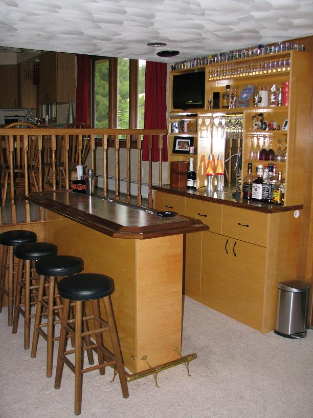 maple bar with full bar back and swing out tv walnut bar rail and a brass foot rail